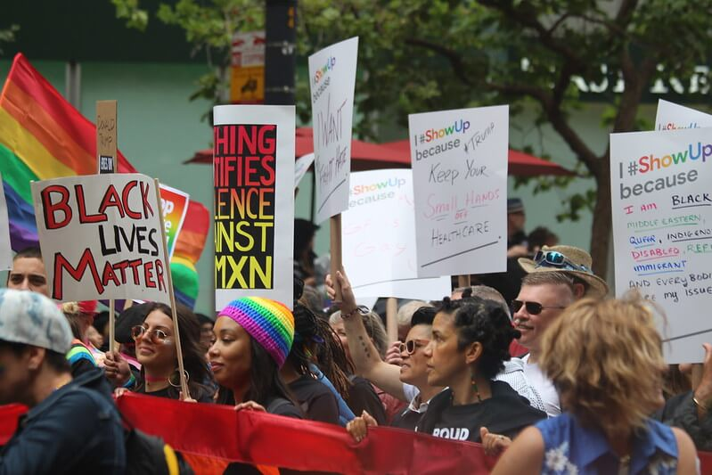 Black Lives Matter protest with pride flags.